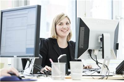 Blonde woman working behind a computer smiling at the camera